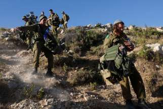 Israeli soldiers take part in an operation to locate three Israeli teens near the West Bank City of Hebron June 24. A Jerusalem church official urged people to come forward with information on the teens' kidnapping but also urged Israel to keep its respo nse proportionate.