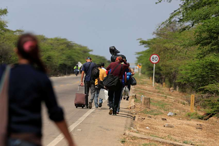 Venezuelans walk on a highway in Paraguachon, Colombia, after crossing the border from Venezuela Feb. 16. Colombian bishops are calling on officials, parishes and the international community to increase efforts to help Venezuelan migrants, who are leaving their country at the rate of at least 50,000 people per month.