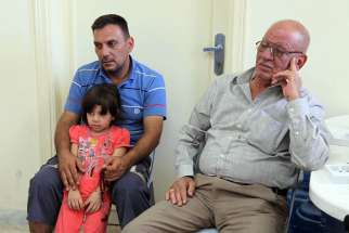 A Christian family who fled from violence in Mosul, Iraq, sit in the room of a church in 2014 in Amman, Jordan. Catholic leaders are describing situations for Iraqi Christian refugees as 'critical and dangerous.'