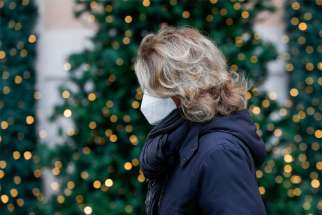 "A woman wears a protective mask as she walks past holiday decorations in Rome Dec. 2, 2020. The Italian bishops have said Christmas Eve ""midnight Mass"" must end before a 10 p.m. nationwide curfew in place by the government to battle COVID-19."