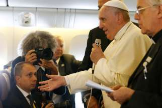 Pope Francis answers questions from journalists aboard the papal flight from Seoul, South Korea, to Rome Aug. 18.