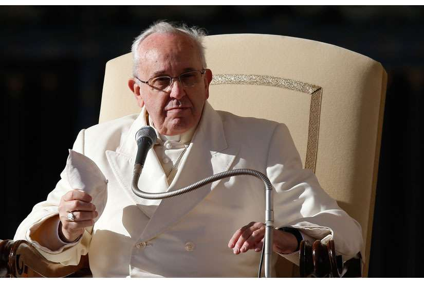 Pope Francis holds his zucchetto as he leads his general audience in St. Peter's Square at the Vatican Dec. 10. In his talk, the pope reviewed the October extraordinary Synod of Bishops on the family.
