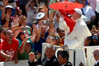 Pope Francis greets pilgrims as he arrives in St. Peter's Square at the Vatican Aug. 12, after an outdoor Mass celebrated by Cardinal Gualtiero Bassetti of Perugia-Citta della Pieve, president of the Italian bishops' conference.