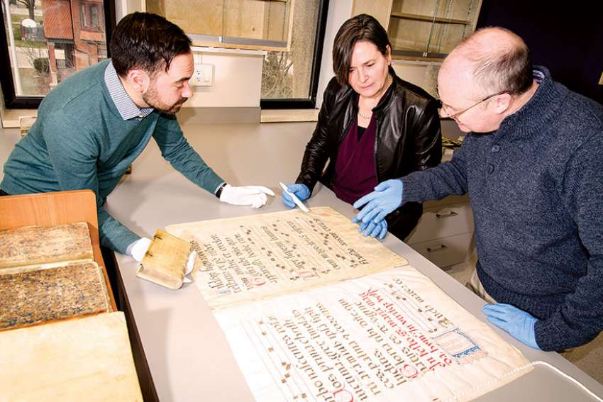James Roussain, Sheril Hook and Noel McFerran (left to right) examine an illuminated text in the new conservation studio at the Kelly Library.