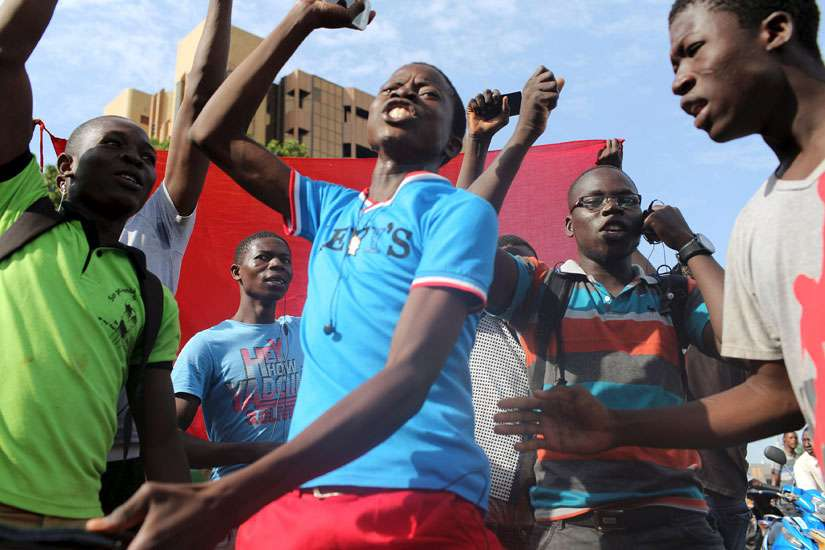 Young men sing the Burkinabe national anthem as they protest the military coup in Ouagadougou, Burkina Faso, Sept. 22.