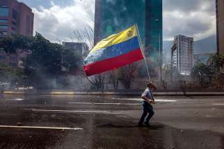 A demonstrator carries Venezuela's flag in Caracas, Venezuela, April 26. After meeting with government representatives, Venezuela's bishops conference reiterated its rejection of government proposal to draft a new constitution.