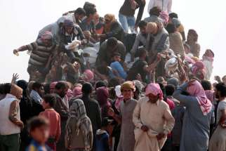 Iraqi refugees that fled violence in Mosul and internally displaced Syrians who fled Islamic State controlled areas in Deir el-Zour buy food and water at the Syrian border near Hassakeh.