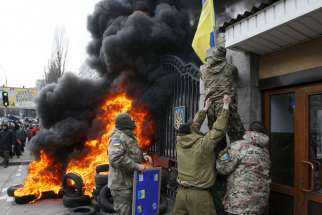 Servicemen from the Aydar battalion throw a Ukrainian flag from the building of Ukraine's Defense Ministry in Kiev during a protest against the disbanding of the battalion in this Feb. 2 file photo.