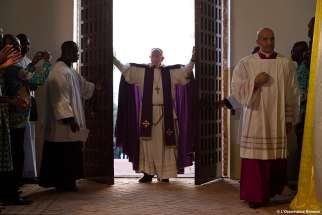 Pope Francis walks through the Holy Door after opening it to begin the Holy Year of Mercy at the start of a Mass with priests, religious, catechists and youths at the cathedral in Bangui, Central African Republic, Nov. 29.
