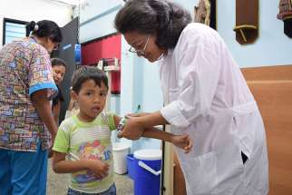A doctor measures the arms of a child attending the local SAMAN nutrition clinic, a partnership between sisters of Our Lady of the Immaculate Conception of Castres and Caritas Internationalis.