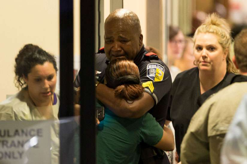 A Dallas police officer is comforted July 7 at Baylor University Hospital's emergency room entrance after a shooting attack. Snipers shot and killed five police officers and wounded seven more at a demonstration in Dallas to protest the police killing of black men in Baton Rouge, La., and a suburb of St. Paul, Minn. Two civilians also were injured in Dallas.