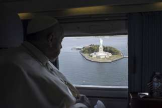 Pope Francis looks out at the Statue of Liberty while flying over New York Harbor on his way from New York to Philadelphia Sept. 26.