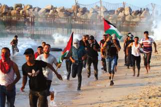Palestinians run for cover from tear gas fired by Israeli troops during a protest along a beach in the Gaza Strip.