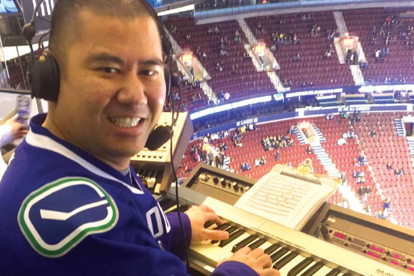 Catholic sports fan Clayton Imoo, pictured playing the organ before a Canucks game in 2016, sees his video blogs, sports commentaries and viral music parodies as an extension of his ministry.