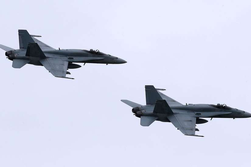 In this May 31, 2014, file photo, two Royal Canadian Air Force F-18 Hornet jets fly over Romania. Canada's new government has decided to stop airstrikes against Islamic State in the Middle East.