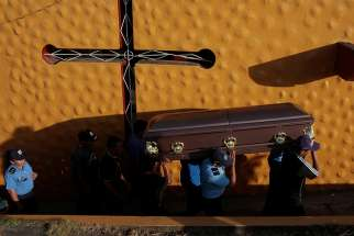 Police officers and relatives carry the coffin of an officer killed during the protests over pension plan reform April 24. The bishops' conference of Nicaragua has accepted an invitation to mediate talks aimed at calming the Central American country.