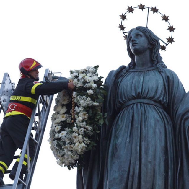 A firefighter places a wreath of flowers on a statue of Mary high atop a column at the Spanish Steps in Rome Dec. 8. The annual tradition marks the feast of the Immaculate Conception.
