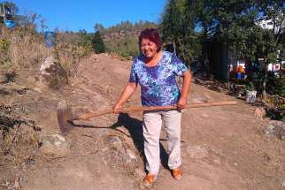 Ana Maria Araya Venegas from the Parish of Santa Rosa de Lavadero, Chile, displays the rake that helped save her house from recent forest fires in this March 13 photo. Prevention has helped parishes survive worst fires in Chile's history.