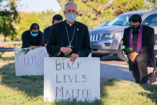 Bishop Mark J. Seitz kneels at Memorial Park in El Paso, Tex.