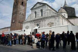 People wait in line outside the Cathedral of St. John the Baptist before the opening of the public exposition of the Shroud of Turin in Turin, Italy, April 19. The shroud, believed by many to be the burial cloth of Jesus, is on display from April 19 through June 24, 2015.