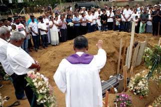 A clergyman prays over the casket of 13-year-old Dhami Brindya during her burial in Negombo, Sri Lanka, April 25, four days after suicide bomb attacks on churches and luxury hotels across the island.