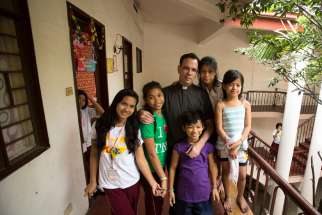 Father Matthieu Dauchez, director of The Blessed Charles de Foucauld Home for Girls, poses with residents Jan. 13 in Manila, Philippines. Father Dauchez said there are between 6,000 to 10,000 street children in metro Manila.