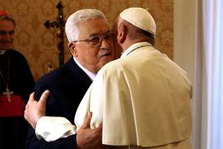 Palestinian President Mahmoud Abbas embraces Pope Francis during a meeting at the Vatican Dec. 3.