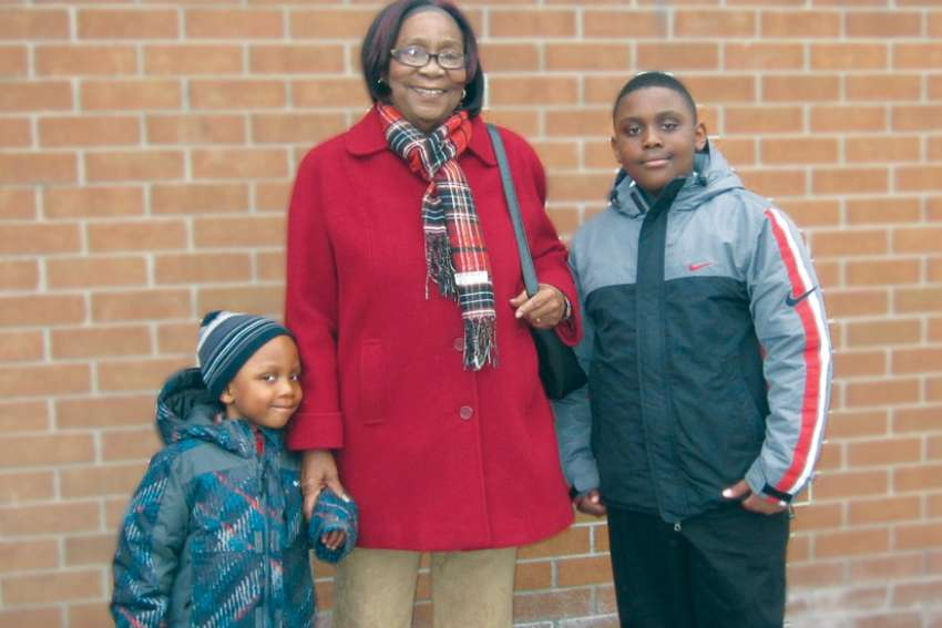Magdalene Massicot and her grandsons pose in front of church in 2013. She died later that year.
