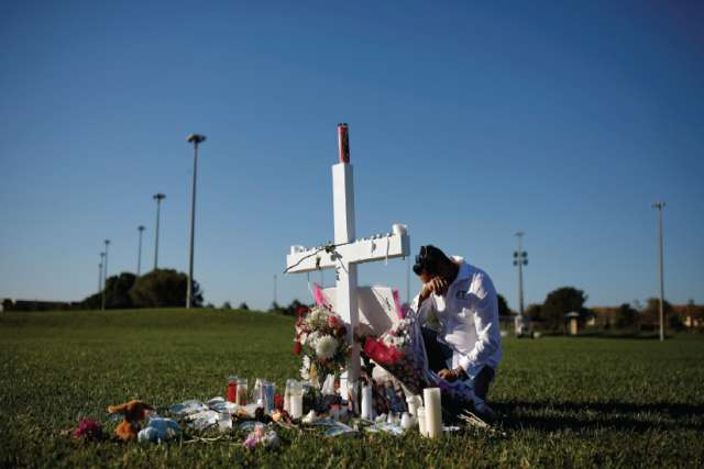 Joe Zevuloni weeps in front of a cross to commemorate the victims of the shooting at nearby Marjory Stoneman Douglas High School in Parkland, Fla.