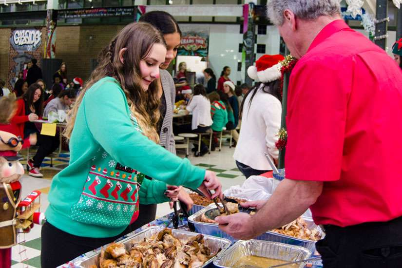 Vanessa Rasile serves food during Bishop Allen Academy's annual Festive Dinner which brings those less fortunate in the community together to share a meal as one big family of friends.