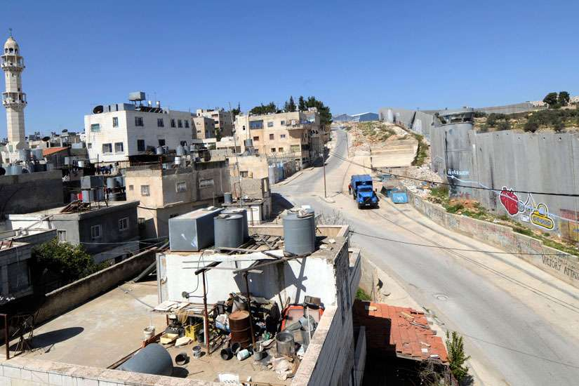 he Israeli separation wall, right, is seen at the edge of the Aida refugee camp, left, in Bethlehem, West Bank.