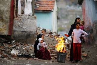 Syrian refugees warm themselves around a fire Dec. 3 in Ankara, Turkey. Martin Mark, right, executive director of Office of Refugees, Archdiocese of Toronto welcomes Canada's pledge to bring in more refugees from the Middle East, but wished the government had consulted with refugee advocates before making its announcement.
