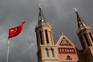 Chinese national flag is pictured in a file photo in front of a Catholic church in the village of Huangtugang.