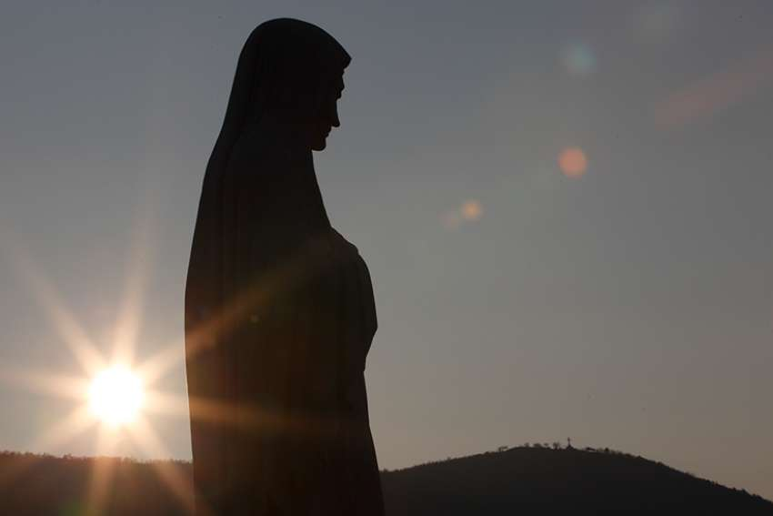 The sun sets behind a statue of Mary on Apparition Hill in Medjugorje, Bosnia-Herzegovina.