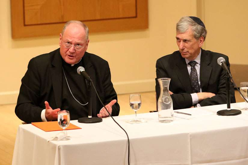 Cardinal Timothy M. Dolan of New York with Chancellor Arnold M. Eisen of the Jewish Theological Seminary of America in New York City, responds to a question during the annual John Paul II Center Lecture for Interreligious Understanding at the seminary May 6.