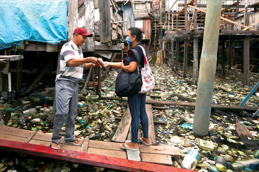 Liliane Tavares de Moura, 44, a parishioner of Our Lady of Perpetual Help Catholic Church in Manaus, Brazil, delivers a protective mask to a resident in one of the city's slums.