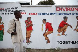 A Liberian man looks at an Ebola sensitization campaign painted on a wall in downtown Monrovia, Liberia, Nov. 19. More cooperation is needed between the international community and faith leaders in stemming the ongoing Ebola epidemic, said a joint commun ique issued by the United Nations and the World Council of Churches.