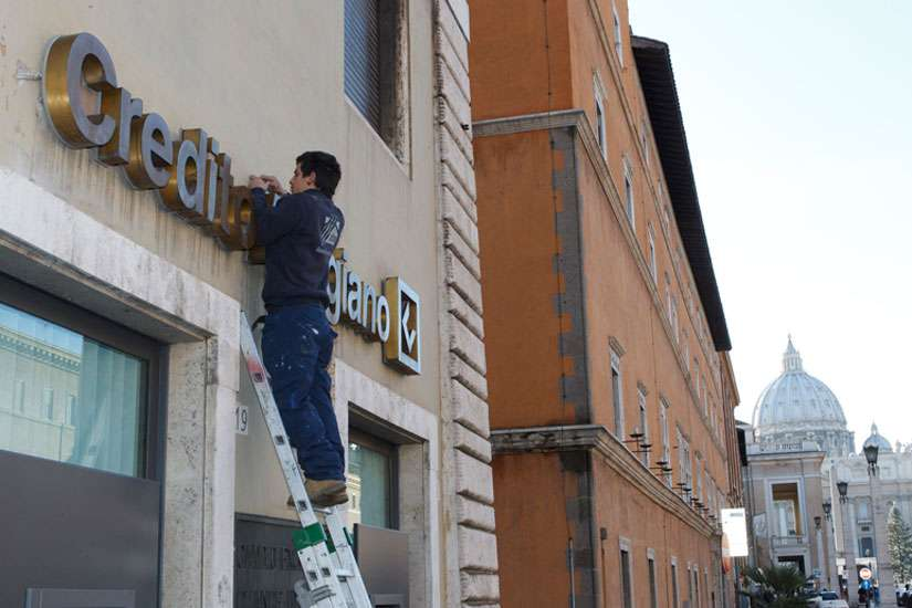A man repairs a bank sign on Via della Conciliazione, the road leading to the Vatican Jan. 29.