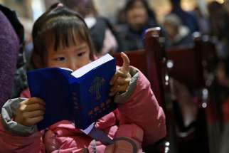 A girl reads a Bible during Mass in the state-approved Xuanwumen Catholic Church in Bejing, China, Dec. 4, 2016.