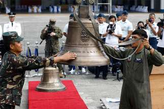 Philippine soldiers use a crane to lift three Balangiga Bells off crates during a turnover ceremony Dec. 11 at Villamor Air Base near Manila. After more than a century, the United States government has returned the three church bells swiped by American forces as war booty from the central Philippine town of Balangiga in 1901.