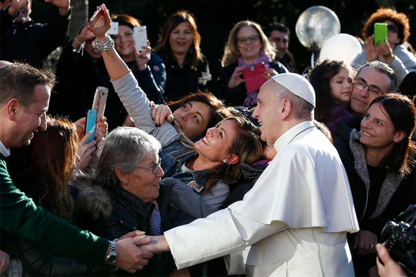Pope Francis poses for a selfie as he greets the crowd outside St. Mary Josefa Church as he arrives to celebrate Mass at the parish in Rome 2017.
