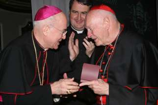 Archbishop Carlo Maria Vigano, then nuncio to the United States, congratulates then-Cardinal Theodore E. McCarrick of Washington at a gala dinner sponsored by the Pontifical Missions Societies in New York in May 2012. The archbishop has since said Cardinal McCarrick already was under sanctions at that time, including being banned from traveling and giving lectures.