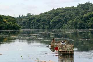 "Men navigate in search of plastic containers to pick out of the polluted waters of the Tiete River in Santana do Parnaiba, Brazil. In a statement during the UN Climate Summit, Cardinal Pietro Parolin observed that ""warming of the climate system is unequivocal. It is a very serious problem which ... has grave consequences for the most vulnerable sectors of society and, clearly, for future generations."""