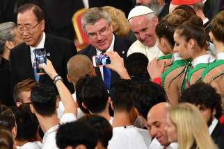 Pope Francis is seen with U.N. Secretary-General Ban Ki-moon, left, and Thomas Bach, president of the International Olympic Committee, during the opening ceremony of a world conference on faith and sport Oct. 5 in the Vatican's Paul VI audience hall.