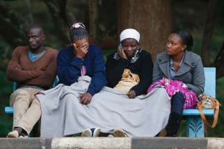 "Wilson Kabwoya, Helen Akani, Agnes Khasandi and Margaret Naishorua wait for the bodies of their loved ones to arrive at a mortuary in Nairobi, Kenya, Dec. 2. Since Somali militants killed 36 non-Muslim quarry workers in early December, Christians in Keny a ""are living in fear, wondering where the next attack will be,"" said Bishop Emanuel Barbara of Malindi."