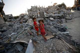 "Two Palestinian sisters walk among the rubble of their destroyed home in the Gaza Strip Aug. 12. A senior Catholic aid official said humanitarians are ""trying to pick of the pieces"" of Gaza's badly destroyed infrastructure, hoping that the truce between Israel and the militant Hamas will hold."
