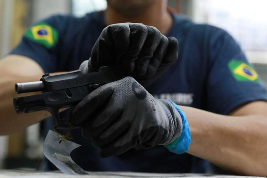 An employee from gun manufacturer Taurus Armas SA works at the company's assembly line in Sao Leopoldo, Brazil. Brazilian President Jair Bolsonaro signed a decree Jan. 15 making it easier for Brazilians to purchase firearms. The decision sparked criticism from several groups in Brazilian society, including some in the Catholic Church.