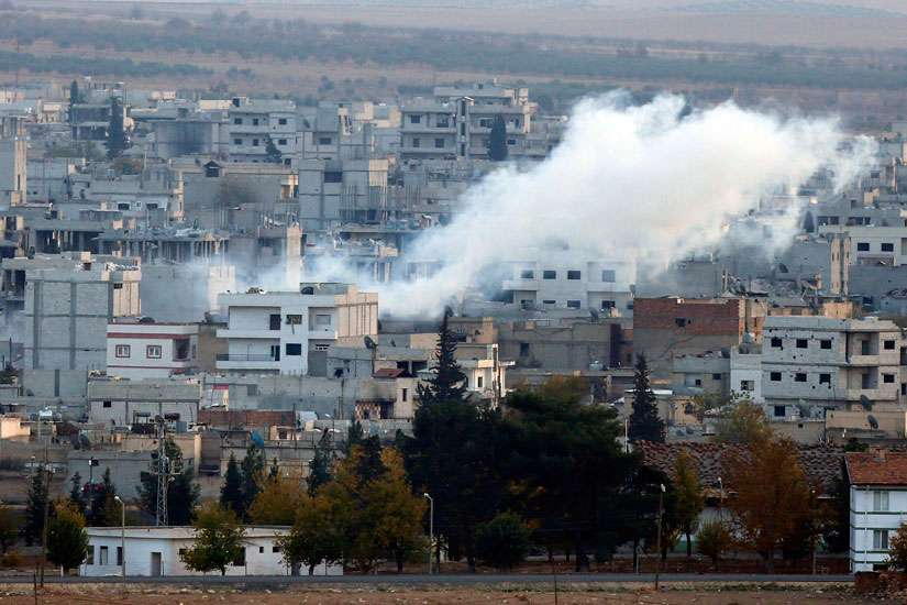 A view shows smoke rising Nov. 20 from a Kobani, Syria, neighborhood damaged by fighting between Islamic State militants and Kurdish forces. The Chaldean Catholic patriarch has appealed to moderate Muslims to more forcefully oppose actions of Islamic Sta te militants.