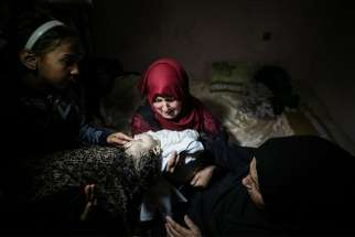 "Palestinian relatives in Gaza City mourn eight-month-old Layila al-Ghandour May 15 who died one day earlier from tear gas inhalation during clashes at the Gaza-Israel border. Archbishop Ivan Jurkovic, the Vatican's observer at U.N. agencies in Geneva, urged people on both sides May 18 to let ""wisdom and prudence prevail."""
