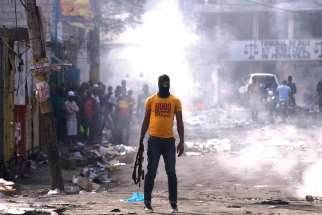 A man holds a weapon next to burning barricades during anti-government protests Feb. 17 in Port-au-Prince, Haiti.